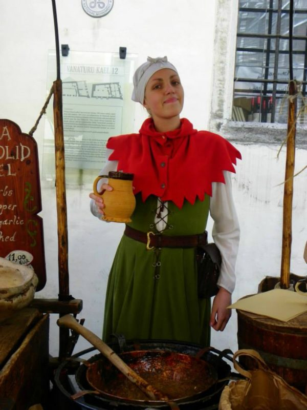 A local shopkeeper selling almonds in medieval dress.