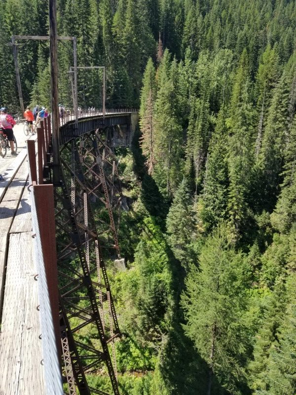 Bike riding across a trestle bridge is one of the fun things you can do along your North Idaho road trip.