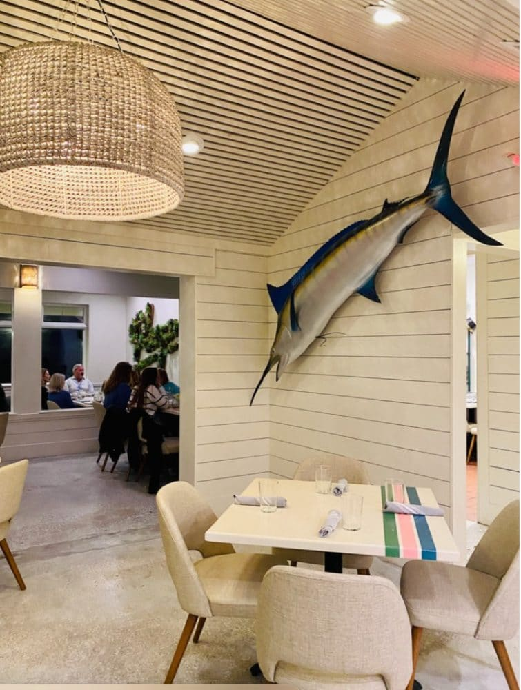 playa restaurant table and chairs with swordfish wall decor