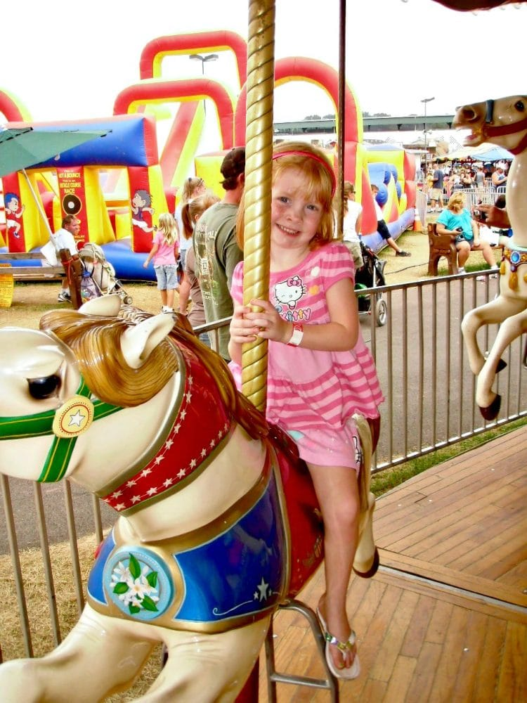 girl riding carousel at west virginia site fair