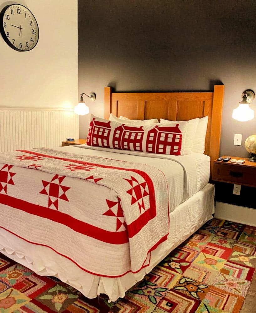bedroom with colorful carpet and red white bed linens